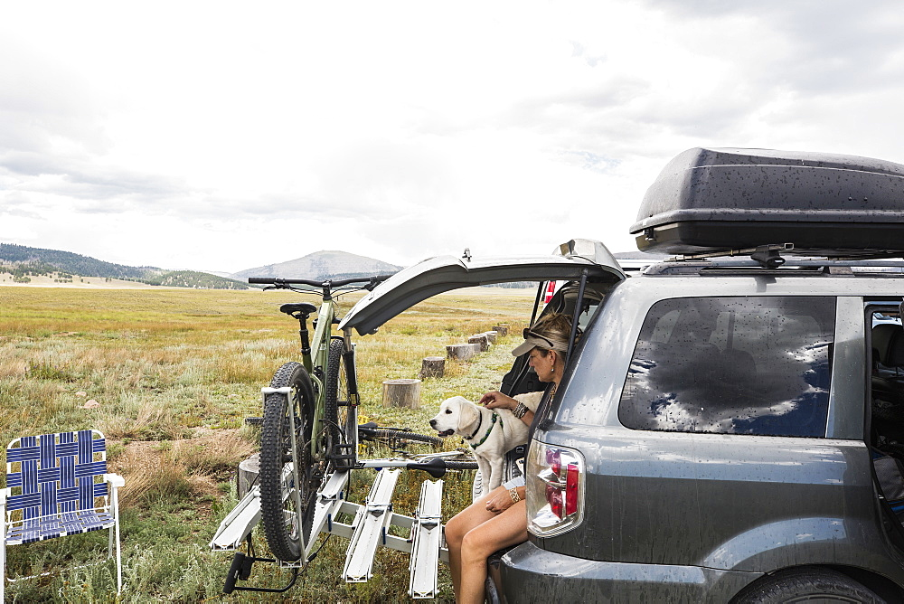 Adult woman on the tailgate of an SUV with her dog, New Mexico, United States - 1174-9023