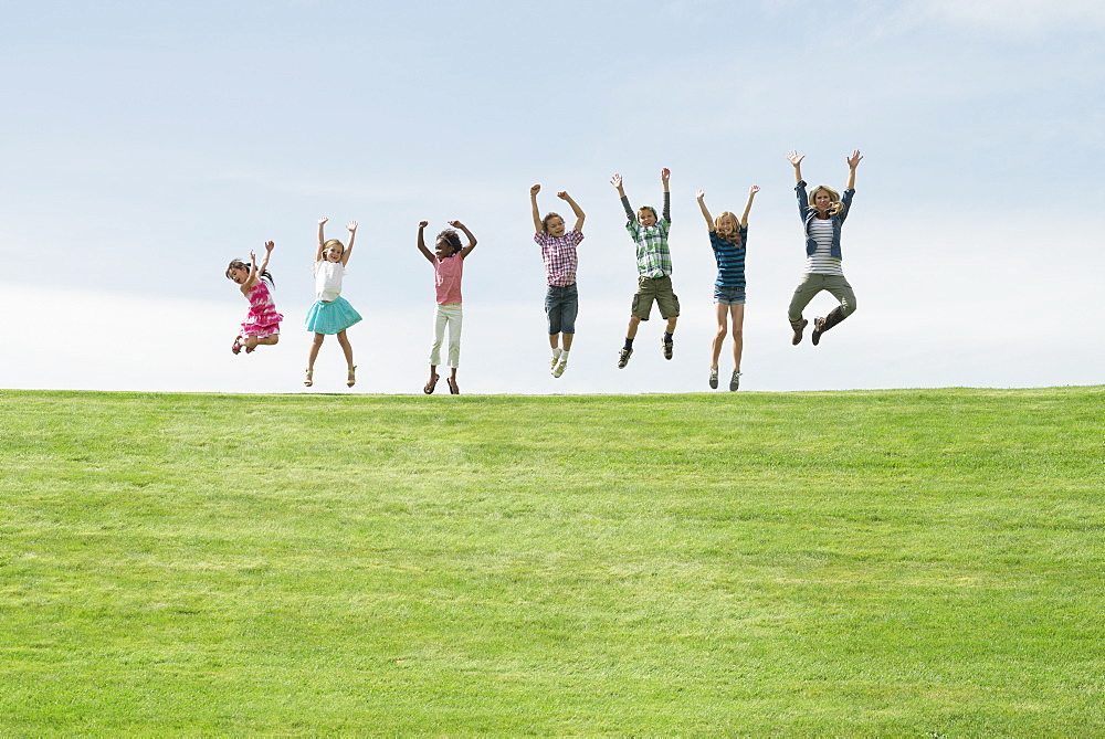 A group of children on the top of a hill, in a row leaping into the air, Utah, USA