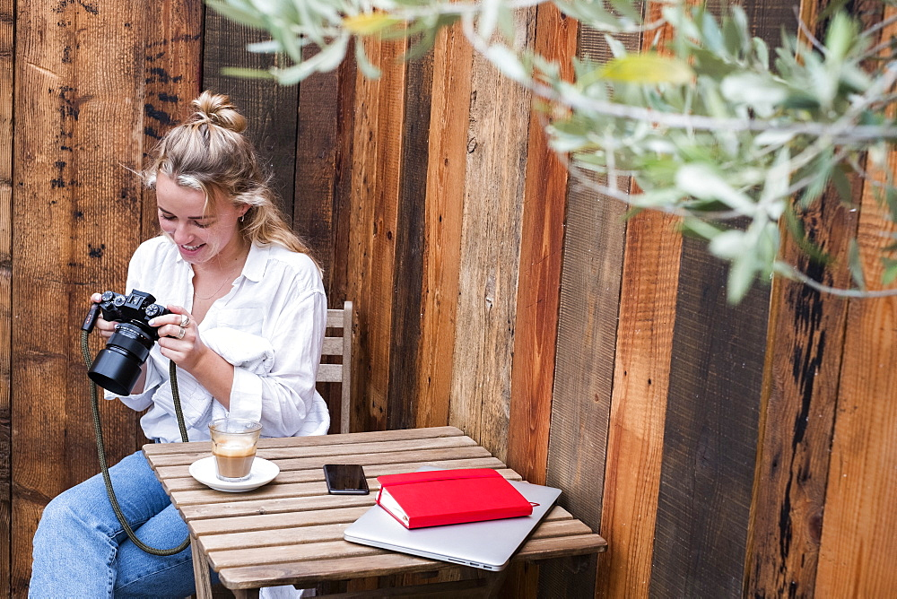 Young blond woman sitting alone at a cafe table, looking at digital camera display, Watlington, Oxfordshire, United Kingdom - 1174-9199