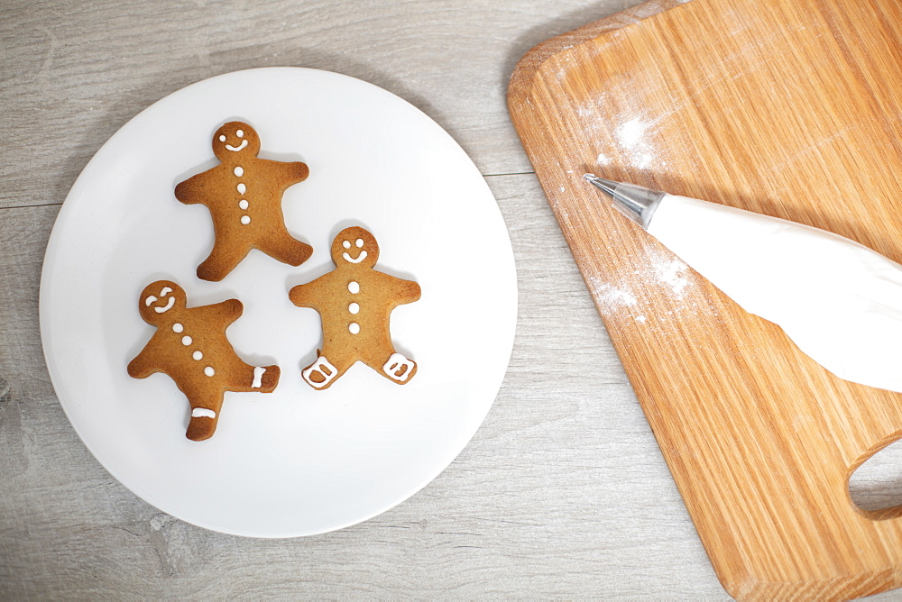 High angle close up of wooden cutting board and Gingerbread Men on a white plate - 1174-9254