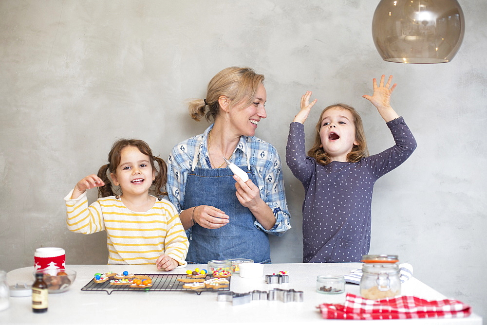 Blond woman wearing blue apron and two girls baking Christmas cookies - 1174-9263