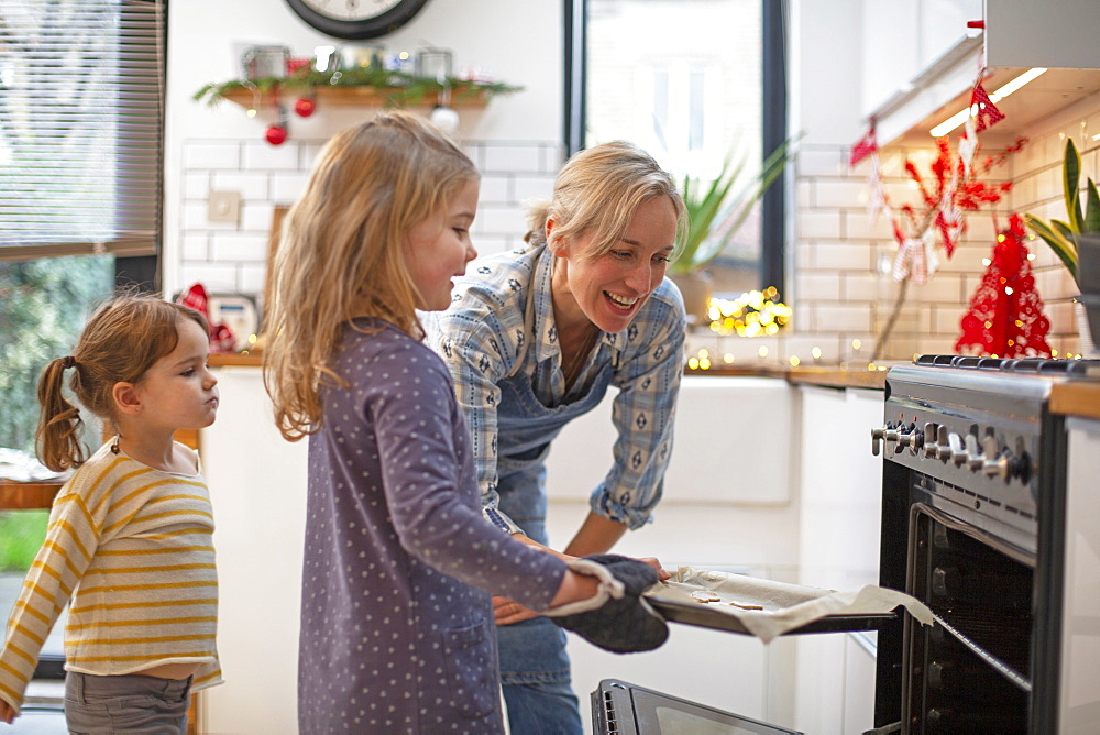 Blond woman wearing blue apron and two girls standing in kitchen, baking Christmas cookies - 1174-9267