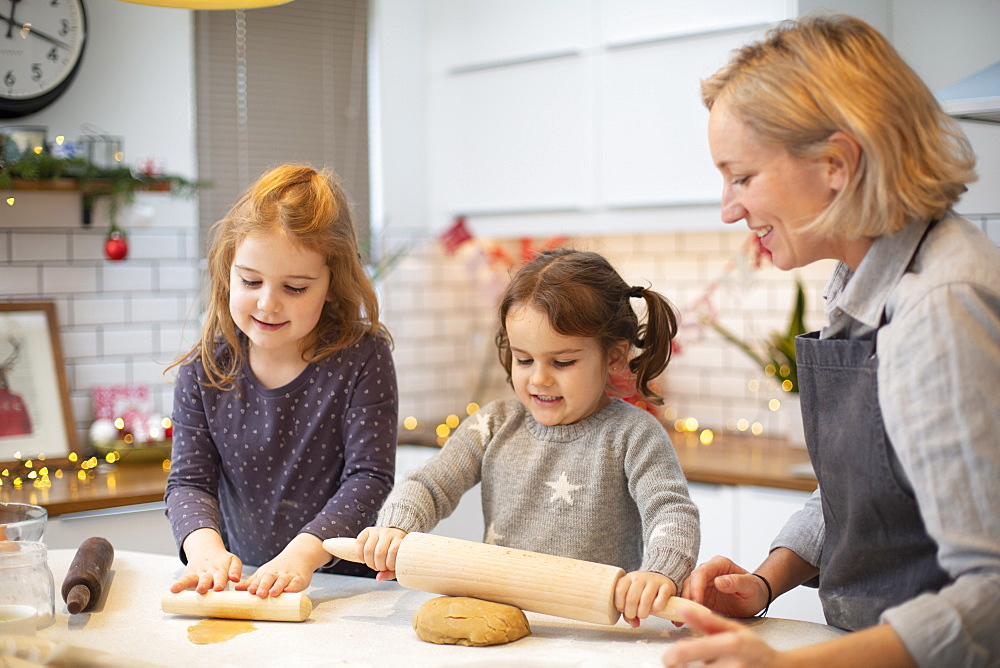 Blond woman wearing blue apron and two girls standing in kitchen, baking Christmas cookies - 1174-9272
