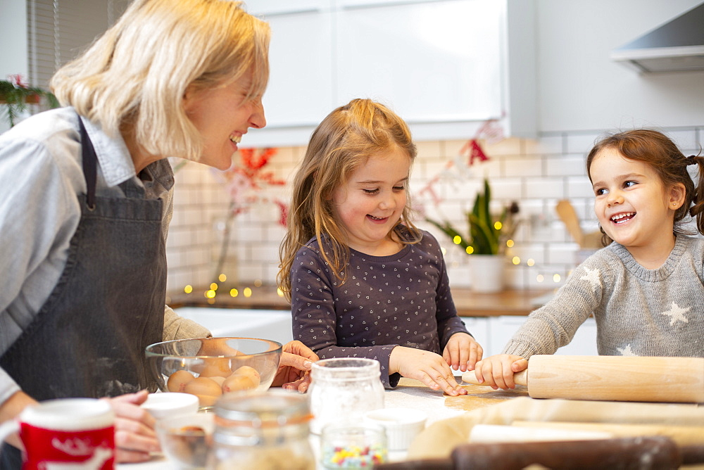 Blond woman wearing blue apron and two girls standing in kitchen, baking Christmas cookies - 1174-9273