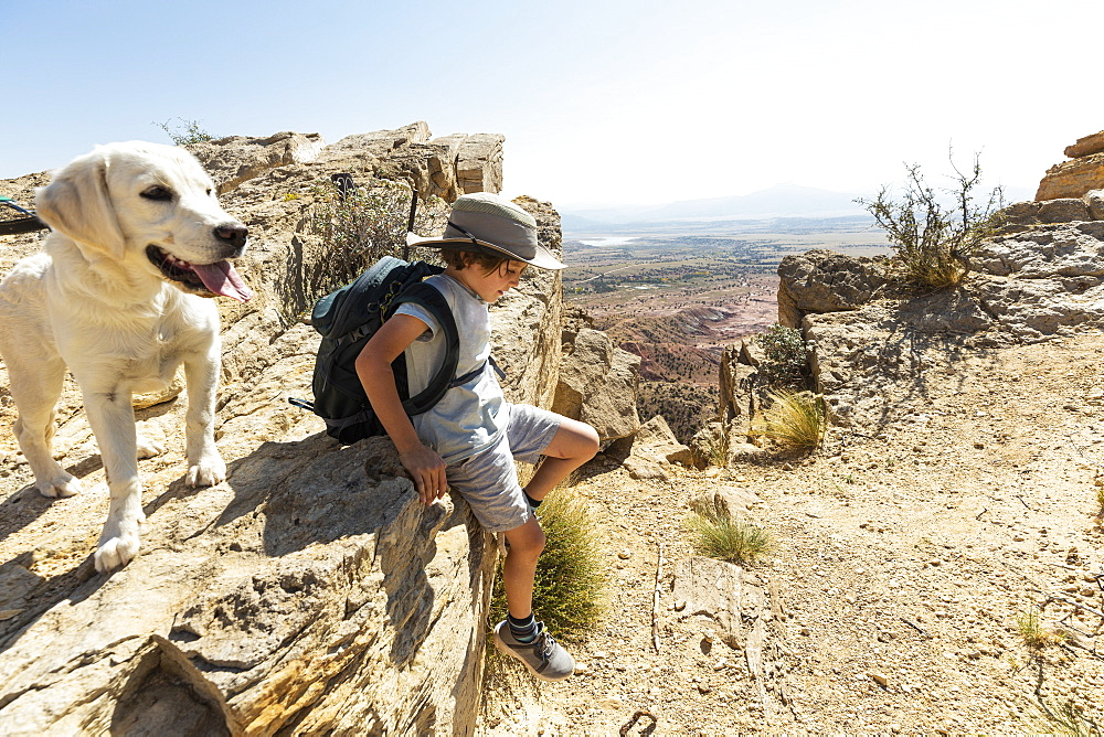 young boy hiking with his dog on Chimney Rock trail, through a protected canyon landscape, New Mexico, United States of America - 1174-9331