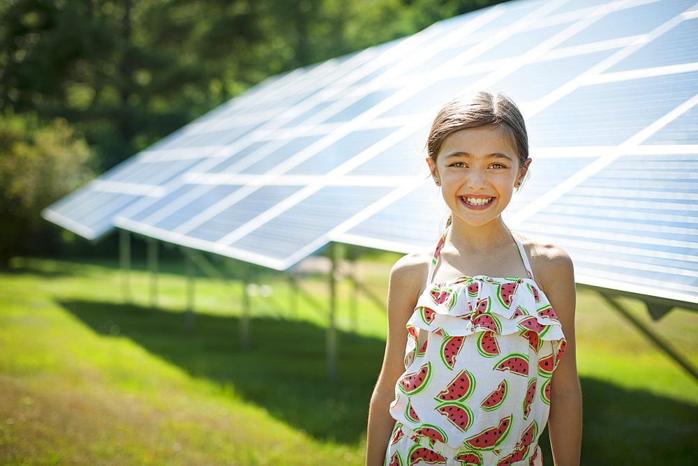 A child in the fresh open air on a sunny day, beside solar panels at a farm, New York state, USA