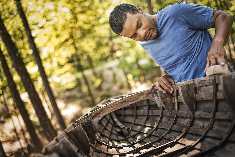 A young man repairing and sanding a traditional wooden rowing boat, New York state, USA