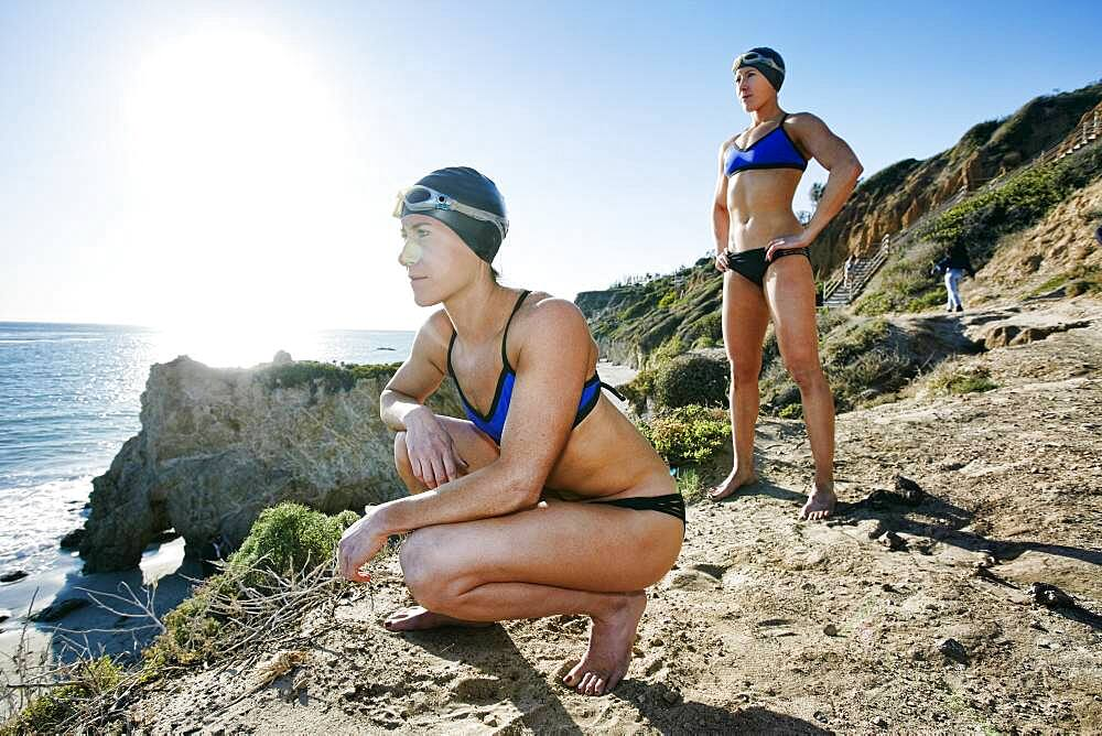 Two sisters, triathletes in training in swimwear, swimhats and goggles. - 1174-9949