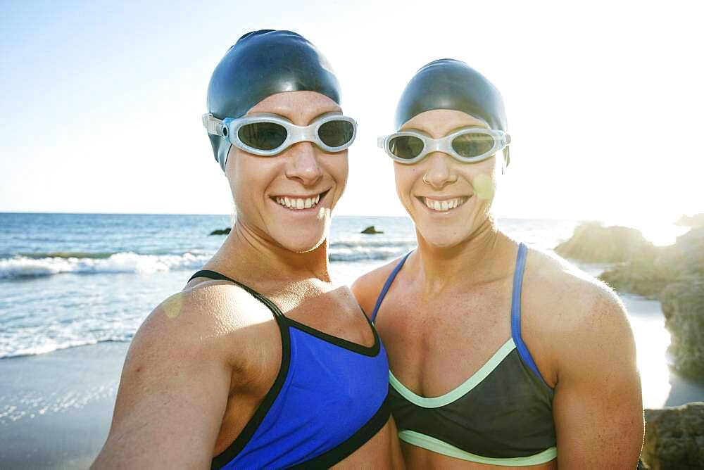 Two sisters, triathletes in training in swimwear, swimhats and goggles. - 1174-9954