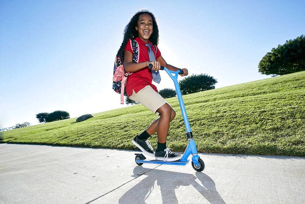 Young mixed race girl in pink shirt and formal tie, wearing a backpack on a scooter - 1174-9965