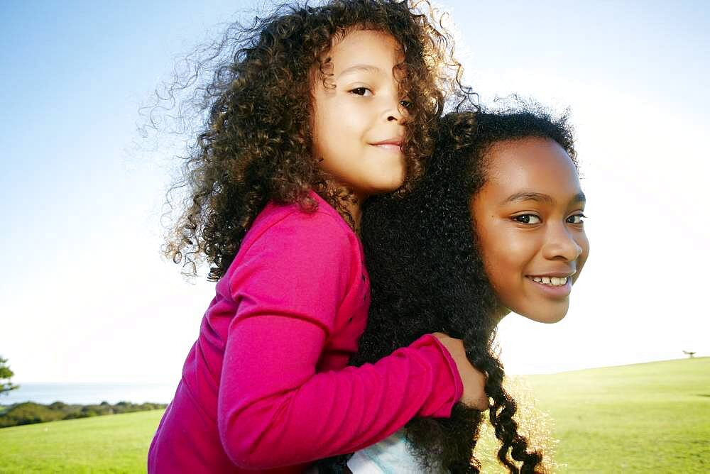 Young mixed race girl giving a younger sister a piggyback - 1174-9971