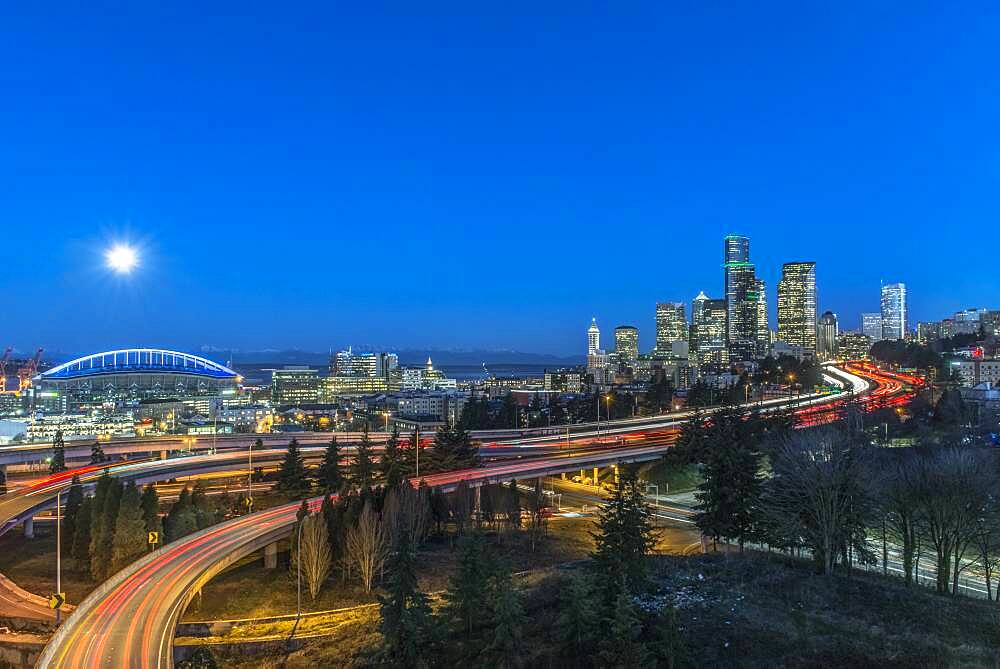 The city skyline of Seattle at night, road and bridge, downtown buildings lit up in moonlight. - 1174-9995
