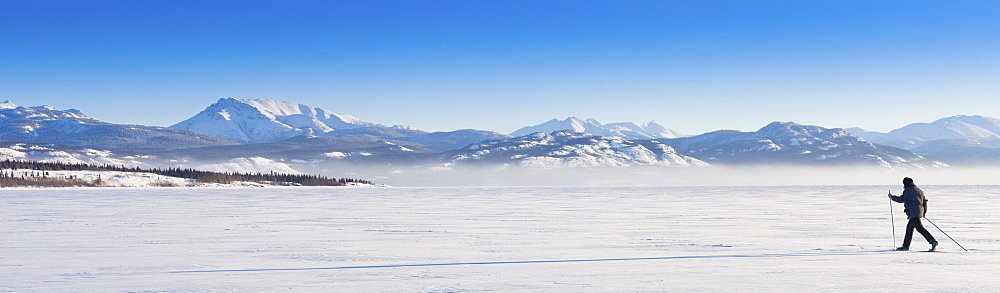 Cross country skier casting long shadow on untouched powder snow in a wide open wilderness landscape.