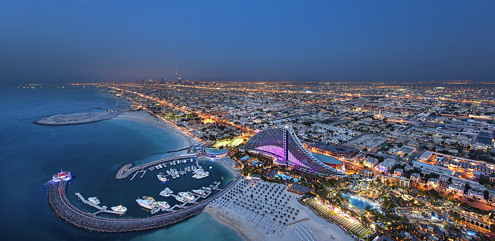 Cityscape of Dubai, United Arab Emirates at dusk, with coastline of Persian Gulf and marina in the foreground, Dubai, United Arab Emirates