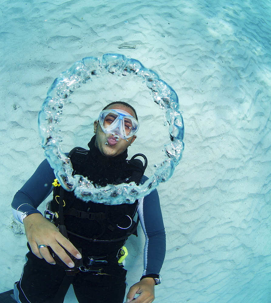 Scuba diver blowing bubble rings.  As the escaping air rises to surface, the decrease in pressure causes the rings of air to expand.