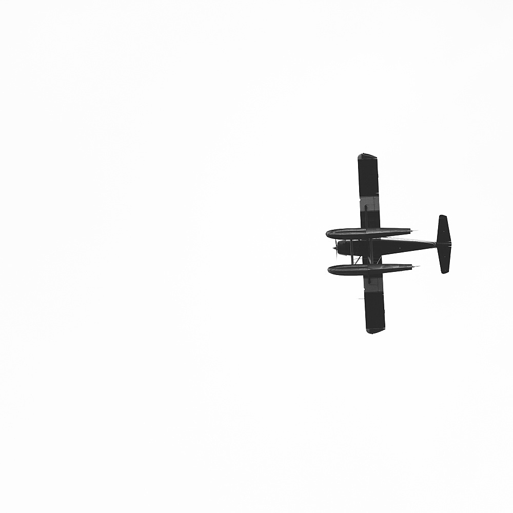 Single engine bush plane flying across open sky (plane is a DeHavilland Beaver), Alaska USA
