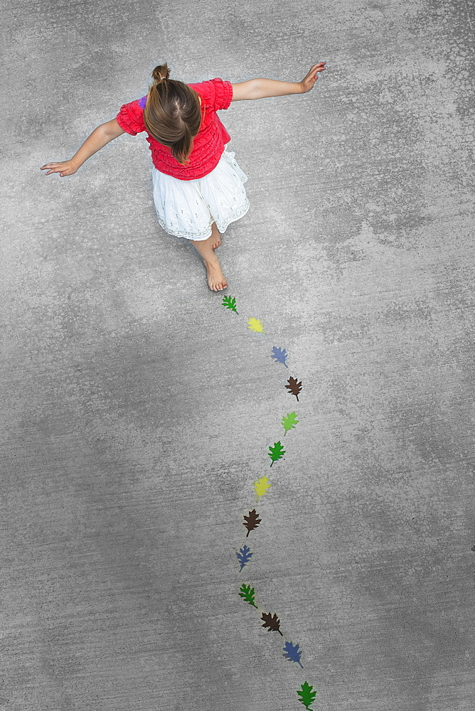 View from overhead of a child creating and walking along a line of coloured leaf shapes, Utah, USA
