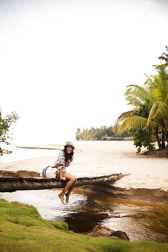 A young woman on a wooden bridge over a small creek on Samana Peninsula in the Dominican Republic, Samana Peninsula, Dominican Republic.