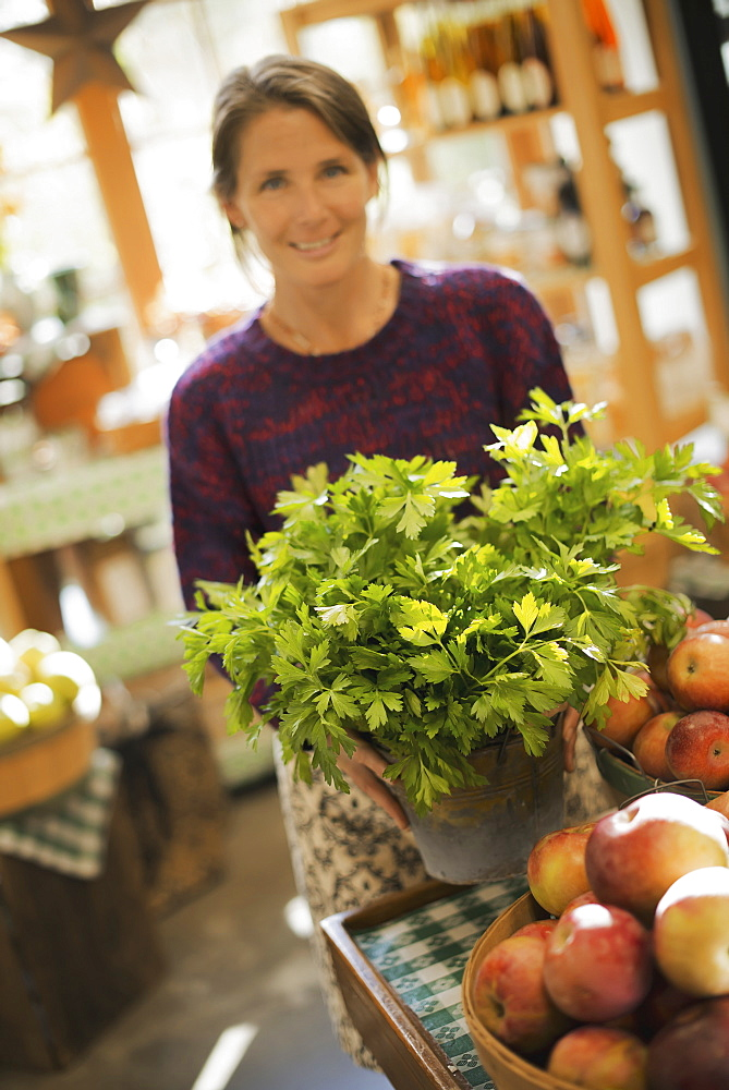 Organic Farmer at Work. A woman working ona farm stand, witha display of fresh produce. Green plants and bowls of apples, Accord, New York, USA