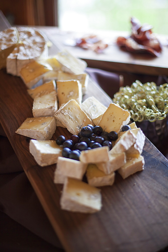 A wedding party meal. A cheeseboard, with soft cheeses cut into triangles, and fresh fruits. Blueberries, Park City, Utah, USA