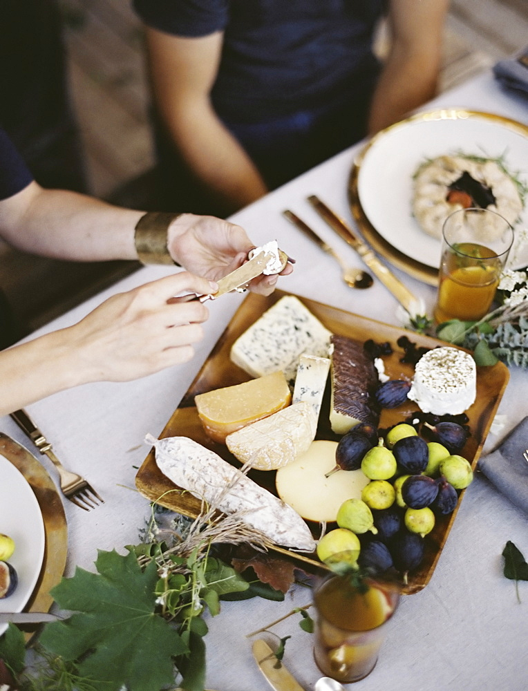 A table laid with a white cloth and place settings seen from above. An organic cheese board with soft and hard cheeses and figs. Two people sitting at the table, Provo, Utah, USA