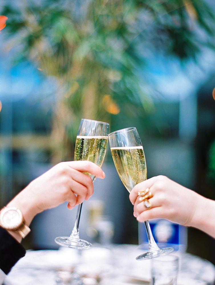 Two women toasting each other with glasses of champagne, England
