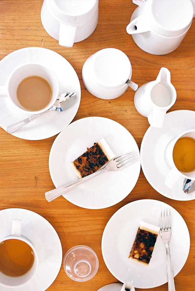 Overhead view of a table set with cups of tea, milk jugs and two slices of fruit cake on plates, England