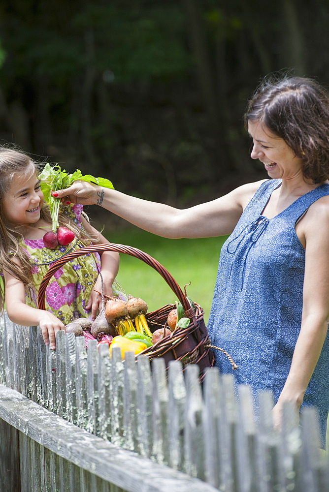 Mother and daughter standing in a garden with a basket of vegetables.