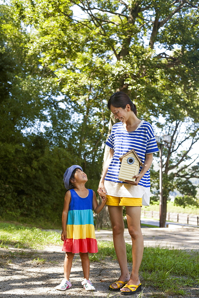 Mother and daughter standing outdoors, holding bird house, Kyoto, Honshu Island, Japan