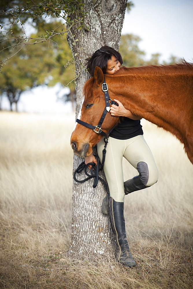 A woman standing under a tree in a field, holding a horse by the halter and stroking its head, Santa Fe, New Mexico, USA
