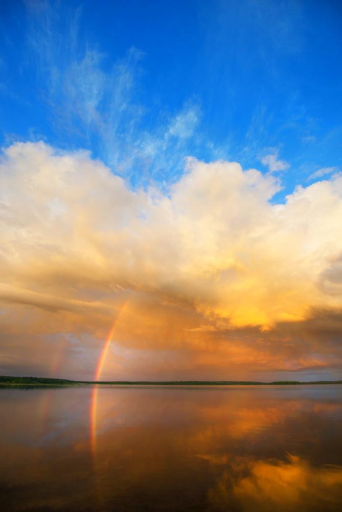 A rainbow and a dramatic cloud formation over a lake, Rainbow, Saskatchewan, Canada