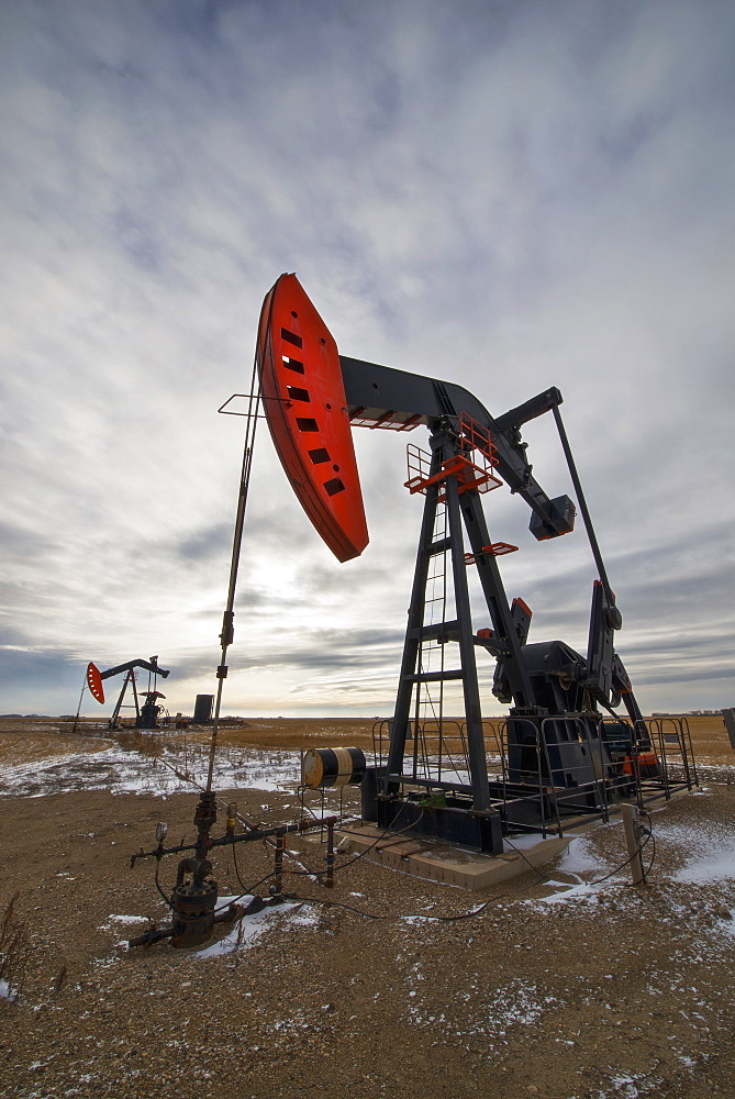 An oil pump jack at a drilling site for oil, an oil field in SaskatchewanOil field pump jack, Saskatchewan, Canada