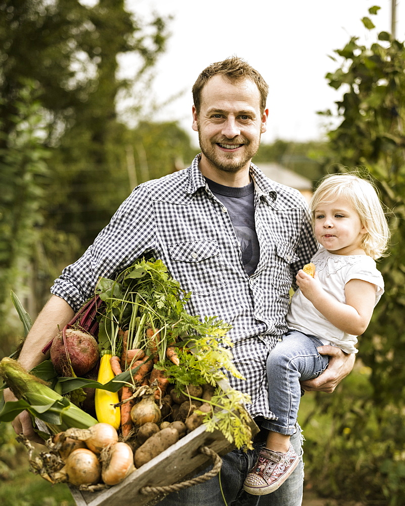 Man standing in his allotment with his daughter, smiling, holding a box full of freshly picked vegetablesAllotment, England