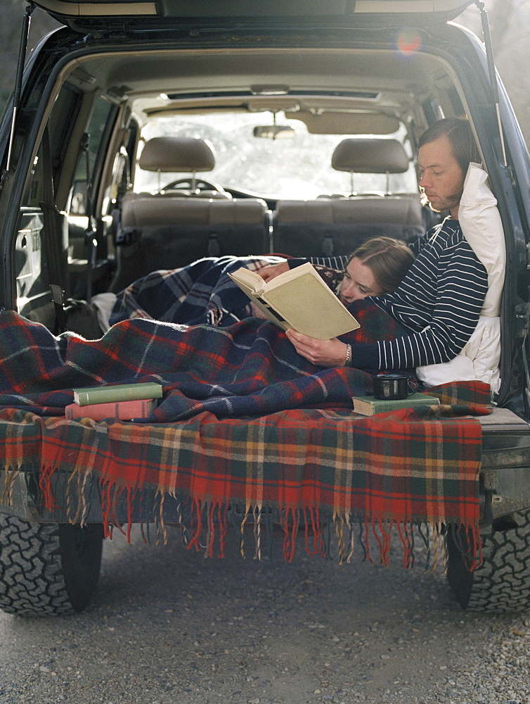 Young couple lying in the back of their car, reading a book, Millcreek, Utah, United States of America
