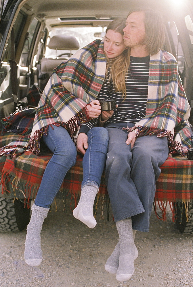 Young couple sitting in the back of their car, Millcreek, Utah, United States of America