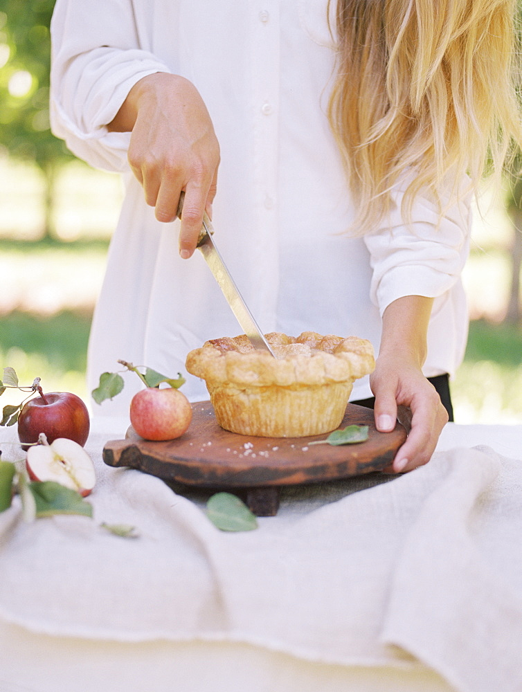 An apple orchard in Utah. Woman standing at a table with food, cutting an apple pie, Sataquin, Utah, United States of America