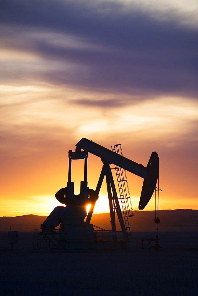 A pumpjack at an oil drilling site at sunset, Oilfield pumpjack, Canada