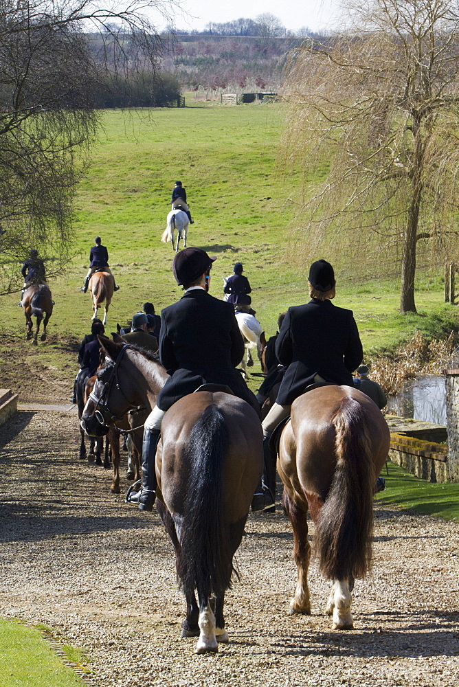 A foxhunt in progress, riders on horseback wearing hard hats riding across countryside, Hunt riders, England