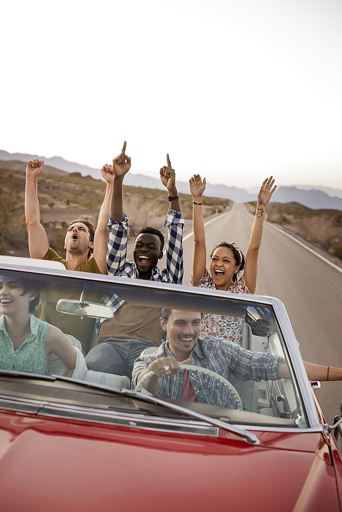 A group of friends in a red open top convertible classic car on a road trip, United States of America