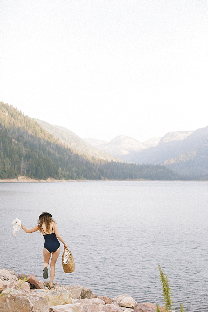 A woman in a swimsuit carrying a basket along the shore of a mountain lake.