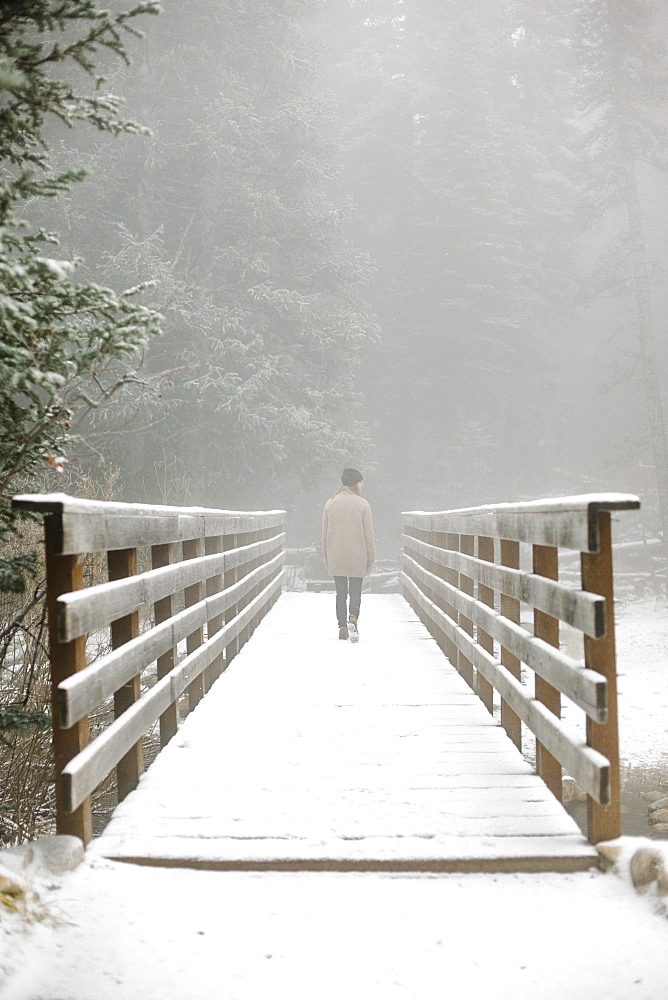 A woman walking on a footbridge in the mountains in snow.