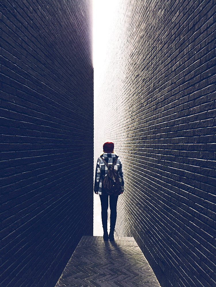 Woman standing in a narrow brick alleyway.