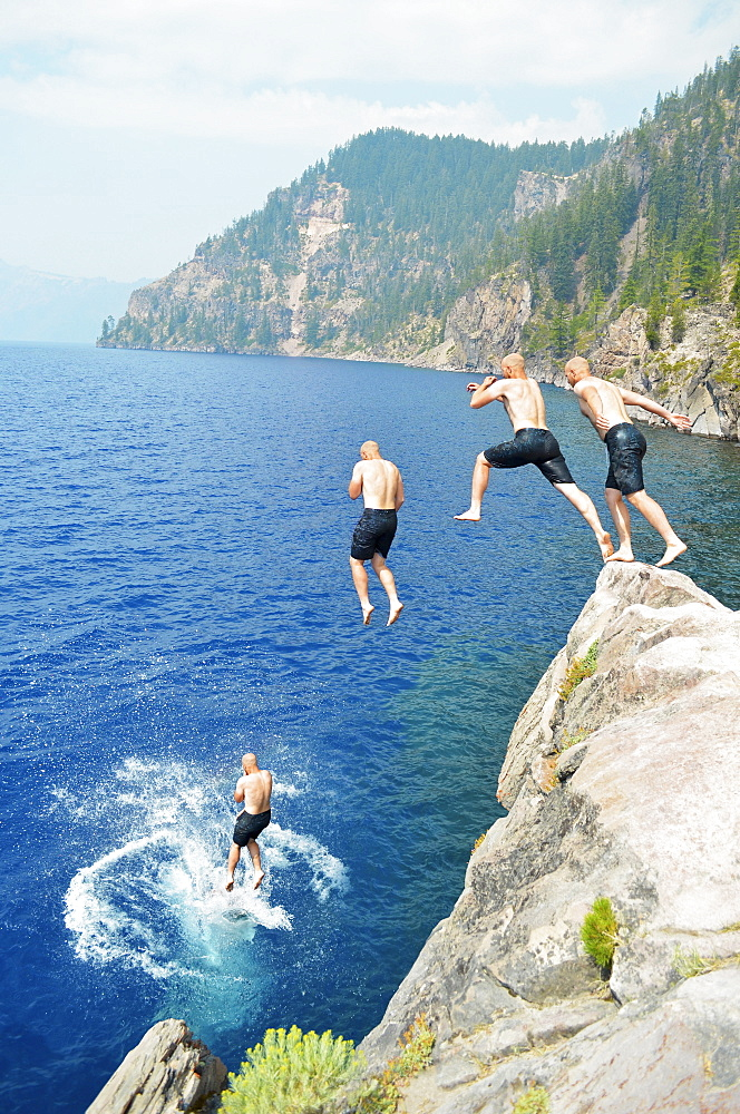 Four men jumping off a rock into a crater lake in Crater Lake National Park, Oregon, USA.