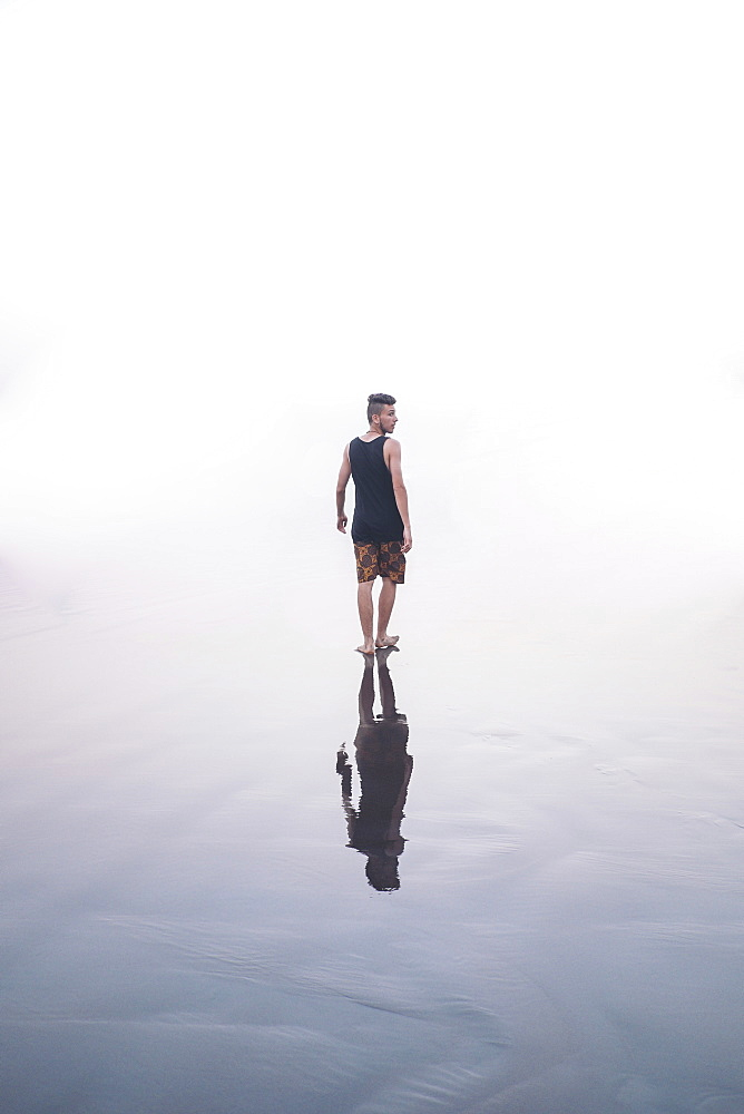 Rear view of a man standing in shallow clear water, with a reflectikon showing on the water.