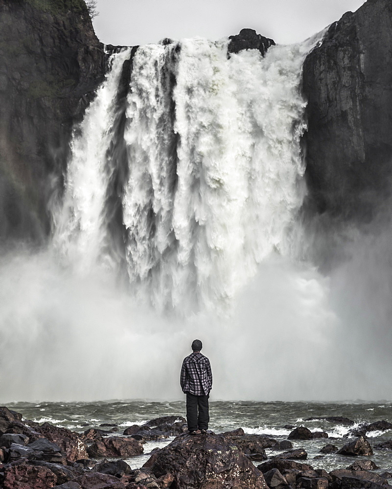 Rear view of a man standing on a rock, looking at a waterfall.