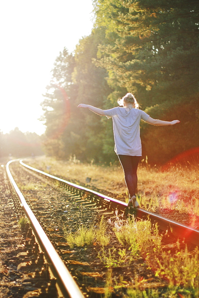 Girl balancing on a railway track.