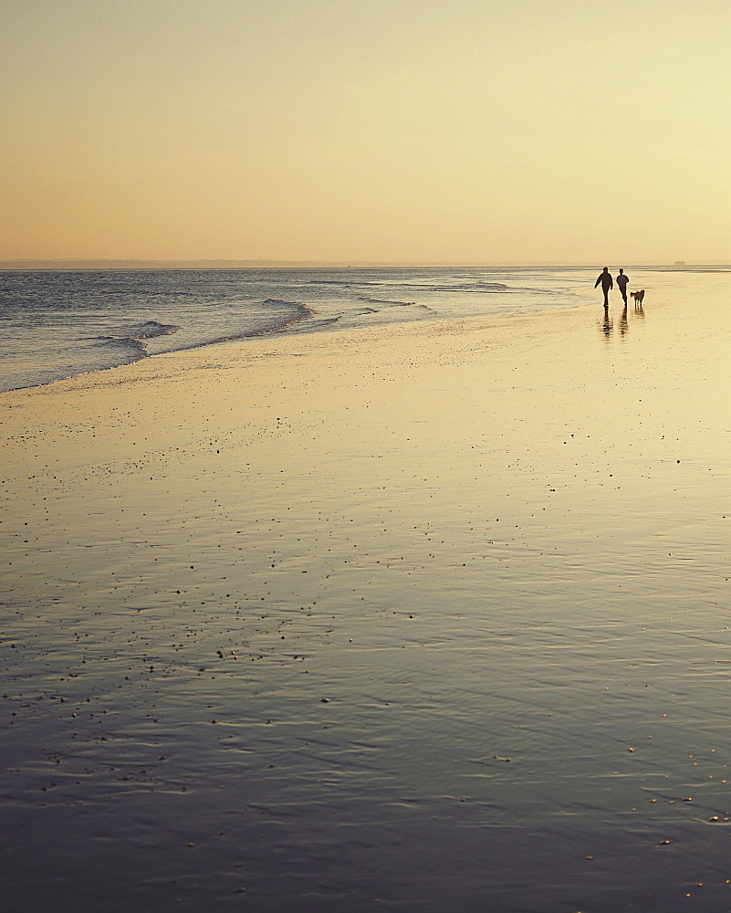 People walking along a sandy beach by the ocean at sunset.