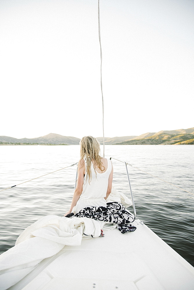 Blond teenage girl sitting on sail boat.
