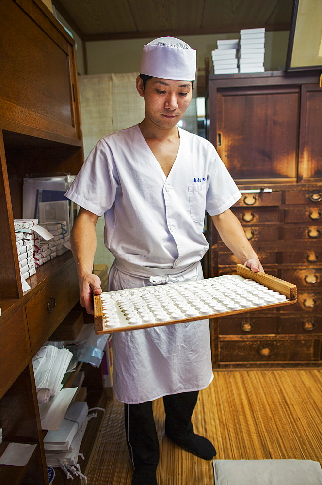 A small artisan producer of specialist treats, sweets called wagashi/ A man holding a tray of sweets, Japan