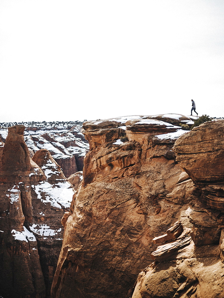 A person standing on the top of a gorge in winter, looking over the landscape.